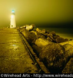 A lighthouse at night with funky concrete forms along the path
