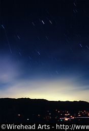 Star trails over a mountain ridge at night