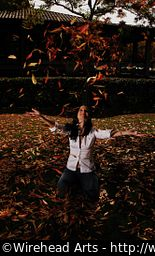 Melinda tossing some leaves up in the air