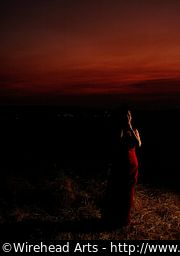 Mimu in a red dress against a red sky, edge lit.